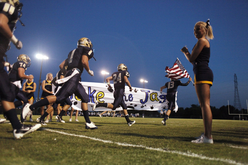 Photo - HH QB Cooper Cloud leads the team onto the field during the high school football game between Heritage Hall and NOAH in Oklahoma City, Friday, Oct. 1, 2010. Photo by Doug Hoke, The Oklahoman.
