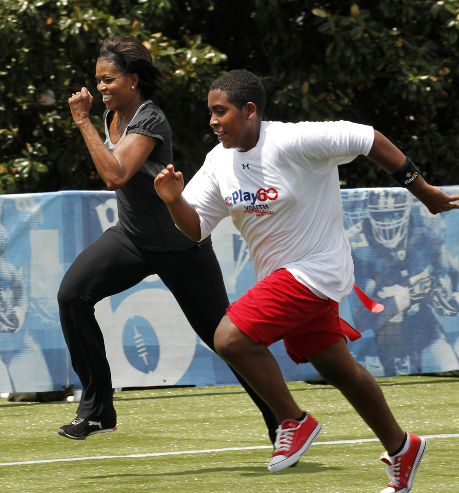 FILE - In this Sept. 8, 2010, file photo, first lady Michelle Obama runs a 40-yard sprint as she participates in the Let\'s Move! Campaign and the NFL\'s Play 60 Campaign festivities with area youth, to promote exercise and fight childhood obesity in New Orleans. Michelle Obama has a new look, both in person and online, and with the president\'s re-election, she has four more years as first lady, too. The first lady is trying to figure out what comes next for this self-described