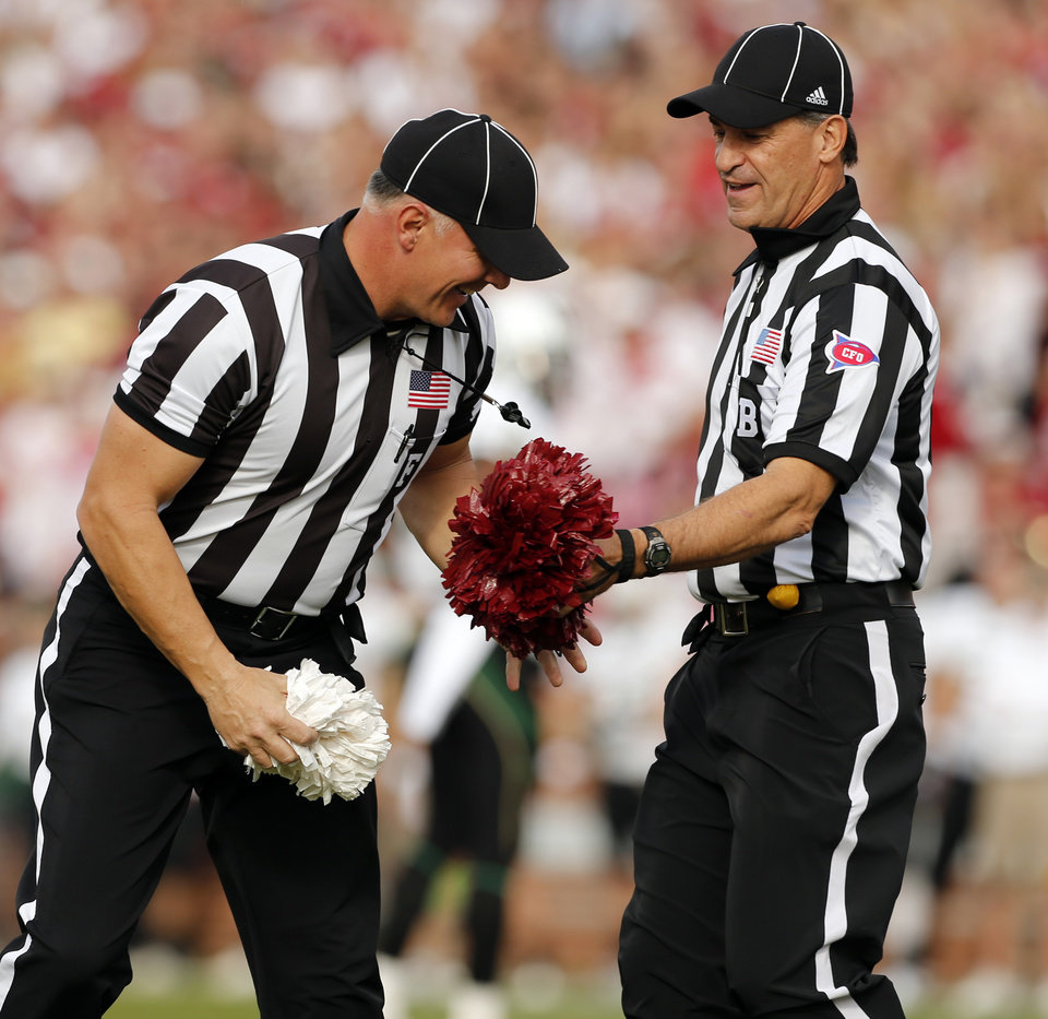 Referees retrieve wind blown pom pons that delayed the game in the first half during the college football game between the University of Oklahoma Sooners (OU) and the Baylor University Bears (BU) at Gaylord Family-Oklahoma Memorial Stadium in Norman, Okla., Saturday, Nov. 10, 2012. Photo by Steve Sisney, The Oklahoman