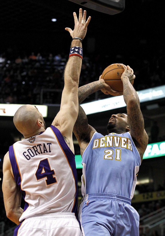 Denver Nuggets' Wilson Chandler (21) shoots against Phoenix Suns' Marcin Gortat (4), of Poland, in the first half during an NBA basketball game on Monday, Nov. 12, 2012, in Phoenix.(AP Photo/Ross D. Franklin)