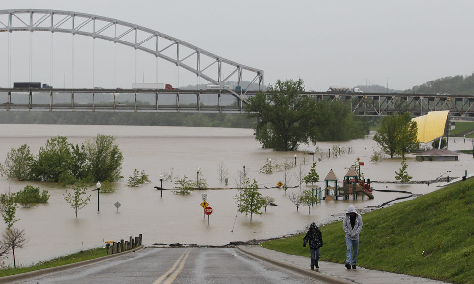 Photo - Residents leave the Riverfront Amphitheater that is surrounded by floodwater from the Ohio River in New Albany, Ind., Wednesday, April 27, 2011. (AP Photo/Darron Cummings)