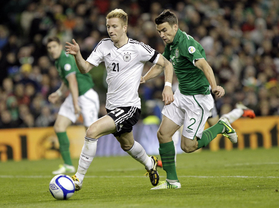 Photo -   Germany's Marco Reus, left, runs past Republic of Ireland's Seamus Coleman during their World Cup Group C qualifying soccer match at the Aviva Stadium, Dublin, Ireland, Friday, Oct. 12, 2012. (AP Photo/Peter Morrison)