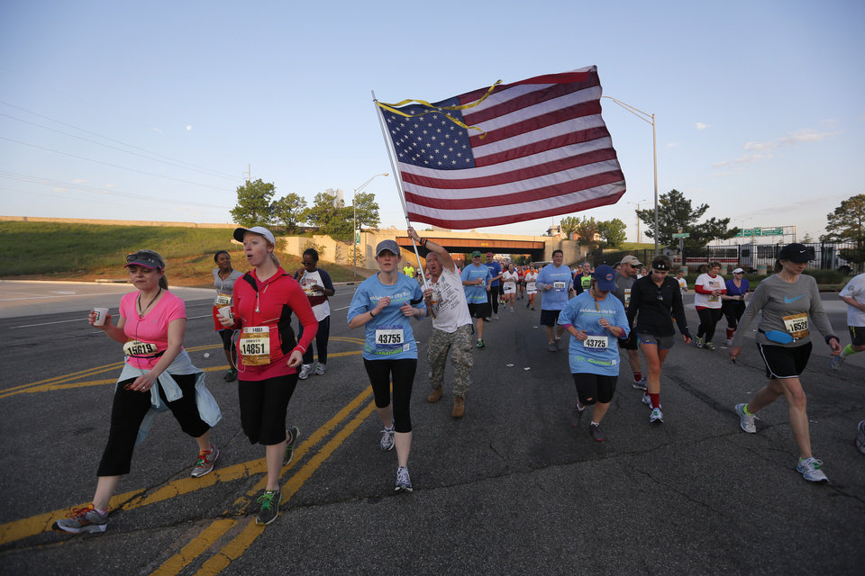 Photo - Runners make their way east on NE 4th St. as a man waves an American flag during the Oklahoma City Memorial Marathon in Oklahoma City, Sunday, April 28, 2013.  Photo by Garett Fisbeck, For The Oklahoman