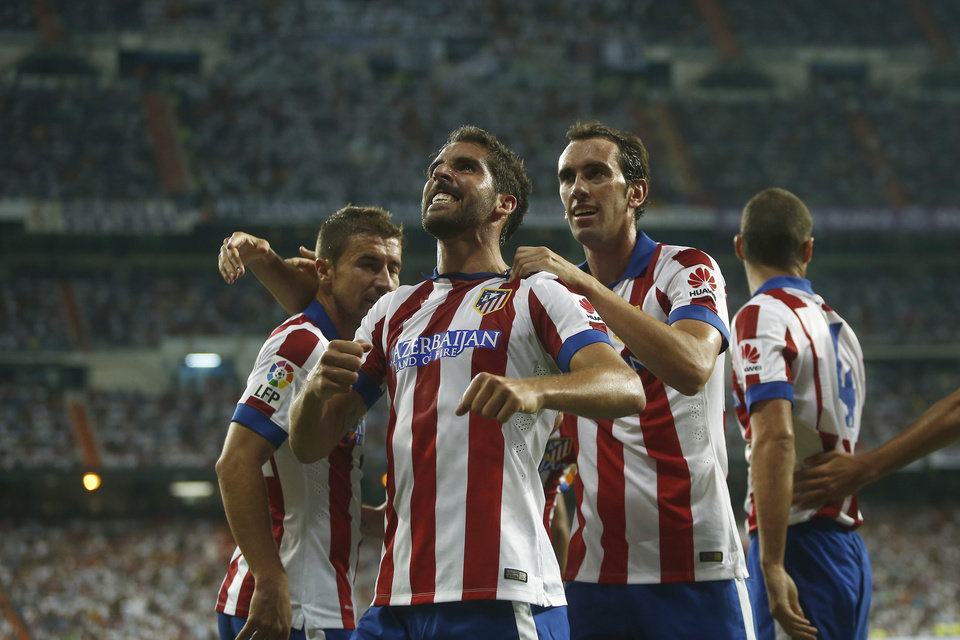 Photo - Atletico's Raul Garcia, center, celebrates his goal with teammates during a Spanish Supercup first leg soccer match against Real Madrid at Santiago Bernabeu stadium in Madrid, Spain, Tuesday, Aug. 19, 2014. (AP Photo/Andres Kudacki)