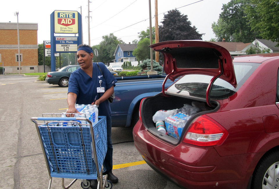 Photo - Sharon Green loads bottled water into her car she bought after Toledo warned residents not to use its water, Saturday, Aug. 2, 2014 in Toledo, Ohio.   About 400,000 people in and around Ohio's fourth-largest city were warned not to drink or use its water after tests revealed the presence of a toxin possibly from algae on Lake Erie. (AP Photo John Seewer)