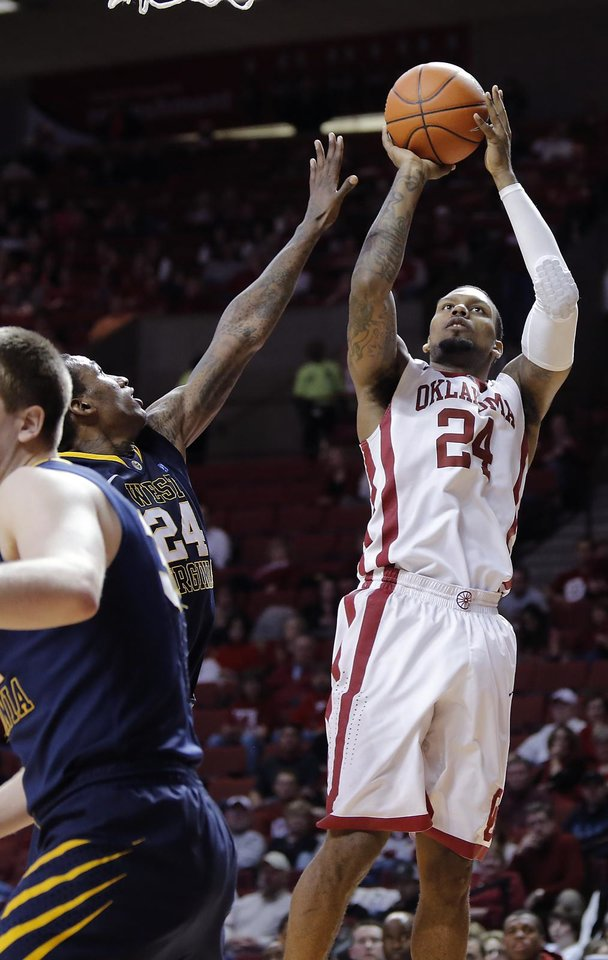 Photo - Oklahoma's Romero Osby (24) shoots the ball over West Virginia 's Aaric Murray (24) during the second half of the college basketball game between the University of Oklahoma Sooners (OU) and the West Virginia University Mountaineers (WVU) at the Lloyd Noble Center on Wednesday, March 6, 2013, in Norman, Okla. Photo by Chris Landsberger, The Oklahoman