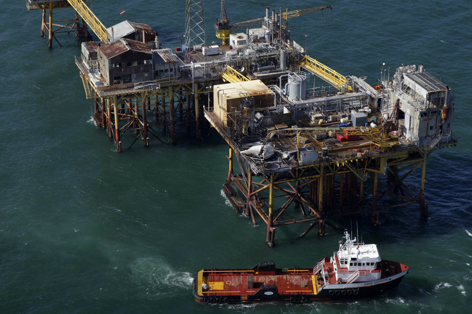 In this aerial photograph, a supply vessel moves near an oil rig damaged by an explosion and fire, Friday, Nov. 16, 2012, in the Gulf of Mexico about 25 miles southeast of Grand Isle, La. Four people were transported to a hospital with critical burns and two were missing. (AP Photo/Gerald Herbert)