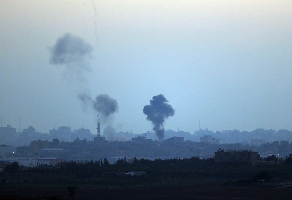 Photo - Smoke rises following Israeli strikes on Gaza, seen from Israel-Gaza Border, Thursday, July 10, 2014. Israel dramatically escalated its aerial assault in Gaza Thursday hitting hundreds of Hamas targets, as Palestinians reported more than a dozen of people killed in strikes that hit a home and a beachside cafe and Israel's missile defense system once again intercepted rockets fired by militants at the country's heartland. (AP Photo/Lefteris Pitarakis)