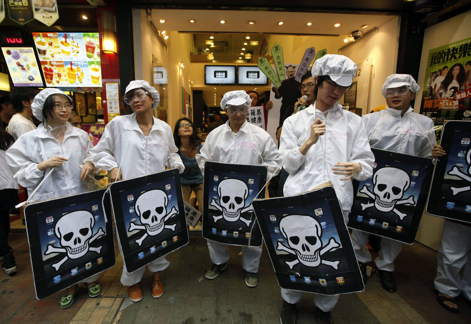 Photo -   FILE - In this Saturday, May 7, 2011 file photo, local and mainland Chinese universities' students, dressed as the Foxconn workers, hold mock iPads with a skeleton print outside an Apple Premium Reseller shop in Hong Kong. Foxconn, the company that makes Apple's iPhones suspended production at a factory in China on Monday, Sept. 24, 2012, after a brawl by as many as 2,000 employees at a dormitory injured 40 people. The fight, the cause of which was under investigation, erupted Sunday night at a privately managed dormitory near a Foxconn Technology Group factory in the northern city of Taiyuan, the company and Chinese police said. (AP Photo/Kin Cheung, File)