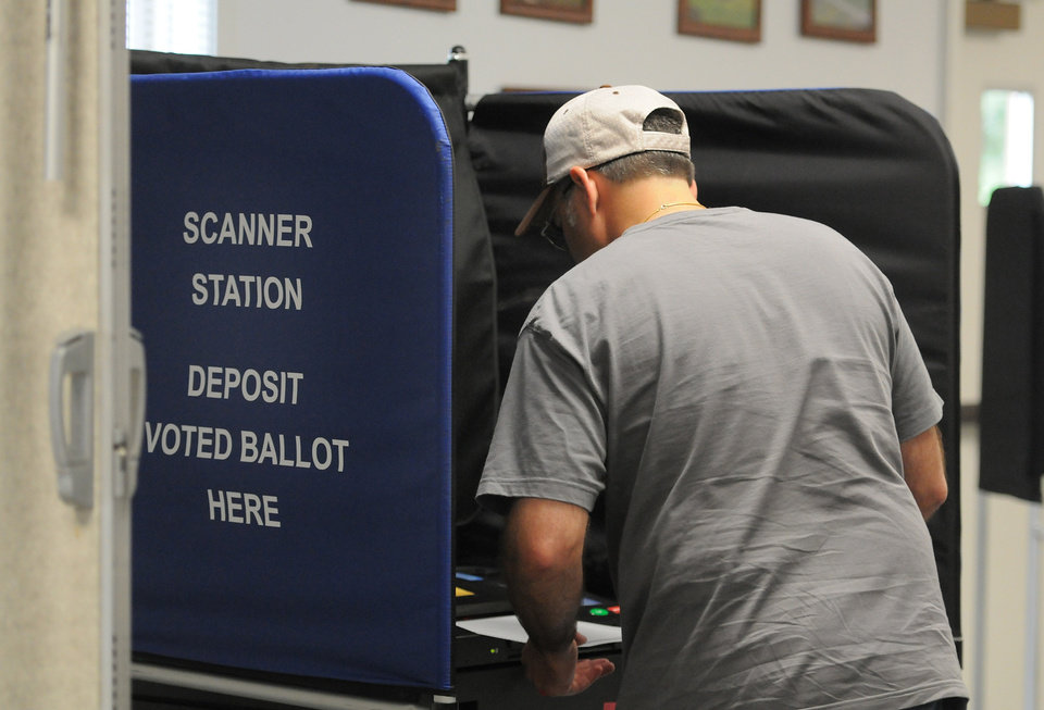 Photo - Joe Diana slides his ballot into a voting machine at the Trenton Municipal Center after voting in the state's congressional primary election Tuesday, June 24, 2014, in Barneveld, N.Y. (AP Photo/Observer-Dispatch, Mark DiOrio) ROME OUT