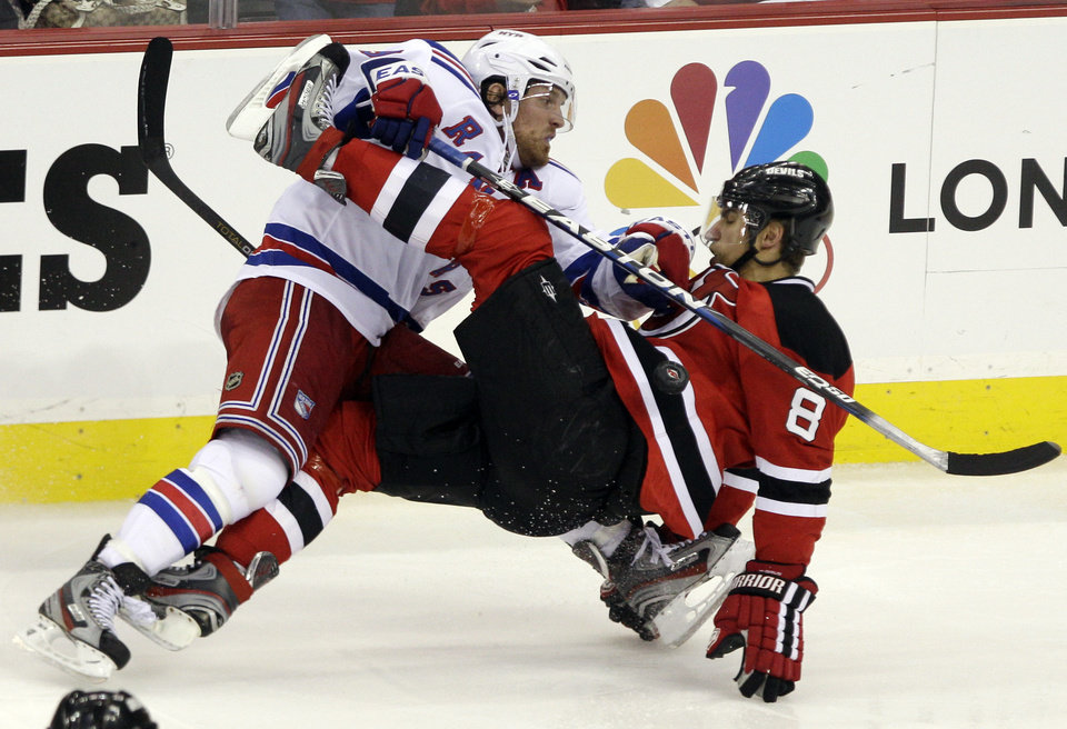 Photo -   New York Rangers center Brad Richards, left, collides with New Jersery Devils defenseman Dainius Zubrus, of Lithuania, during the second period of Game 3 of an NHL hockey Stanley Cup Eastern Conference final playoff series Saturday, May 19, 2012, in Newark, N.J. (AP Photo/Frank Franklin II)
