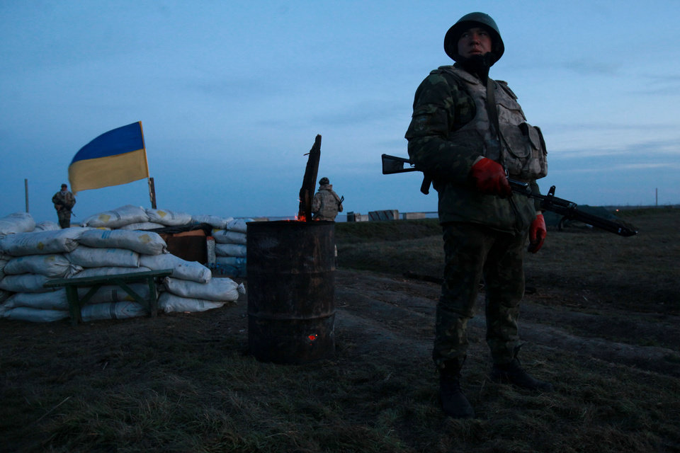 Photo - A Ukrainian soldier guards at a check-point in the village of Chongar in the Kherson region in southern Ukraine close to the Crimean peninsula, Sunday, March 16, 2014. In a referendum watched closely around the world, residents in Ukraine's strategic Crimean Peninsula voted Sunday on whether to demand greater autonomy or split off and seek to join Russia. (AP Photo/Petro Zadorozhnyy)