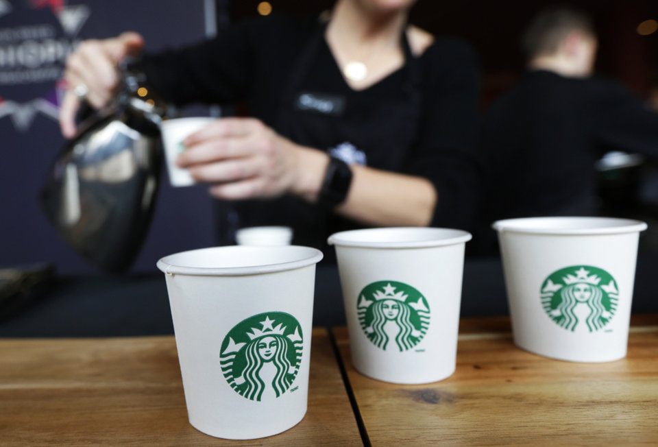 Photo - Sandy Roberts, Starbucks strategy manager for global coffee engagement, pours samples of coffee for shareholders and other guests, Wednesday, March 19, 2014, at Starbucks' annual shareholders meeting in Seattle. (AP Photo/Ted S. Warren)