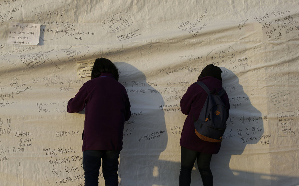Photo - Visitors write messages on the side of a tent, wishing safe return of missing passengers aboard the sunken ferry Sewol at a port in Jindo, south of Seoul, South Korea, Tuesday, April 22, 2014. One by one, coast guard officers carried the newly arrived bodies covered in white sheets from a boat to a tent on the dock of this island, the first step in identifying a sharply rising number of corpses from the South Korean ferry that sank nearly a week ago. (AP Photo/Lee Jin-man)