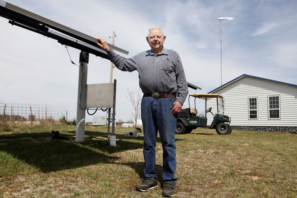 Photo -  Retired utility employee Herb Hill poses for a picture near the solar panels he installed at his home west of Crescent. In the background is his 100-foot-tall wind turbine. Photo by KT King, The Oklahoman    KT King -