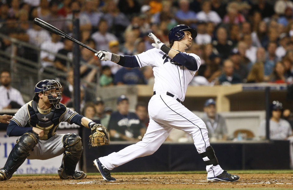 Photo - San Diego Padres' Yasmani Grandal watches his RBI single against the Milwaukee Brewers in the third inning of a baseball game Tuesday, Aug. 26, 2014, in San Diego. The Milwaukee Brewers catcher is Jonathan Lucroy.  (AP Photo/Lenny Ignelzi)