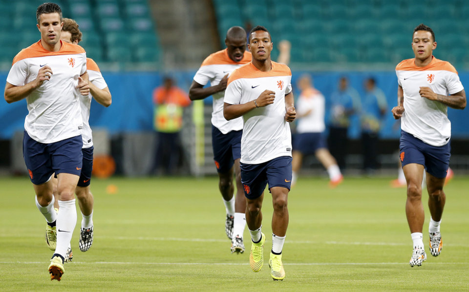 Photo - From left to right foreground: Robin van Persie, Jonathan de Guzman and Memphis Depay warm up during a training session the day before the group B World Cup soccer match between Spain and the Netherlands at the Arena Ponte Nova in Salvador, Brazil, Thursday, June 12, 2014. (AP Photo/Wong Maye-E)