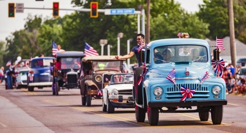 Photo -  Parade participants drive vintage vehicles as they throw candy to spectators during the Bethany Freedom Festival parade.    [Chris Landsberger/The Oklahoman]