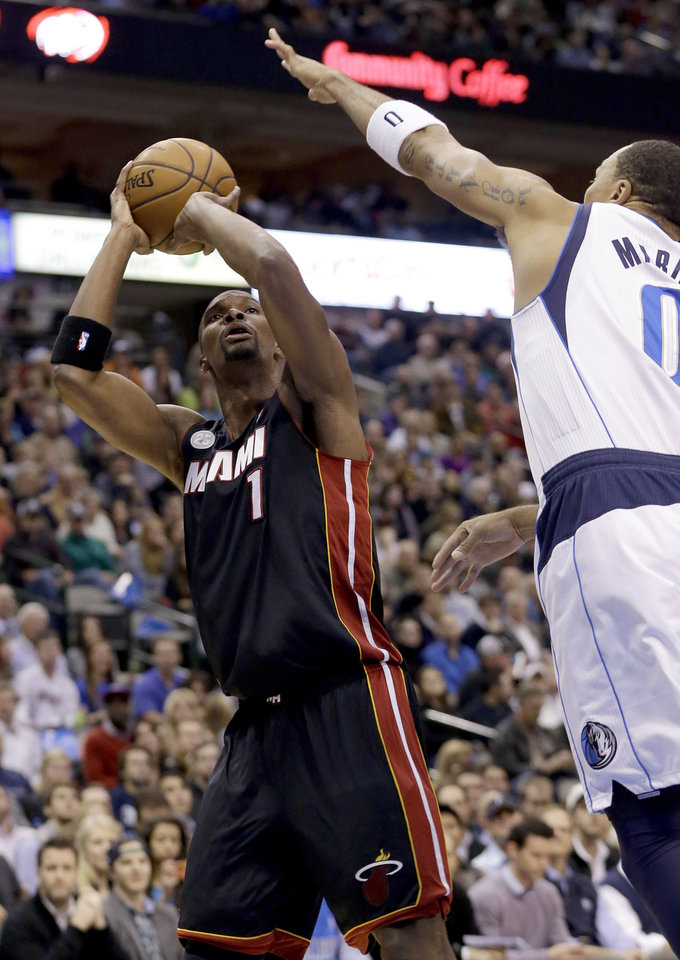 Miami Heat center Chris Bosh (1) shoots against Dallas Mavericks forward Shawn Marion (0) during the first quarter of an NBA basketball game, Thursday, Dec. 20, 2012, Dallas. (AP Photo/LM Otero)