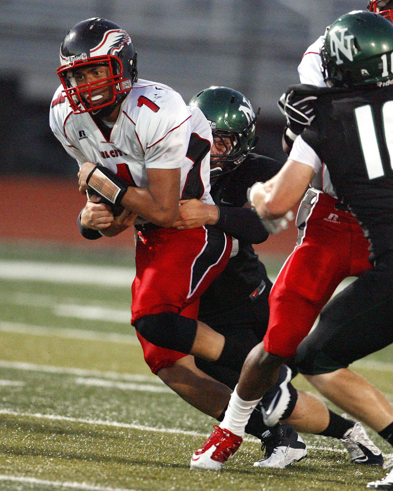 Photo - Del City quarterback Chazten Gonzales (1) is slowed by Norman North's Daniel Moses (34) in high school football at Harve Collins Field on Thursday, Sept. 9, 2010, in Norman, Okla.  Photo by Steve Sisney, The Oklahoman