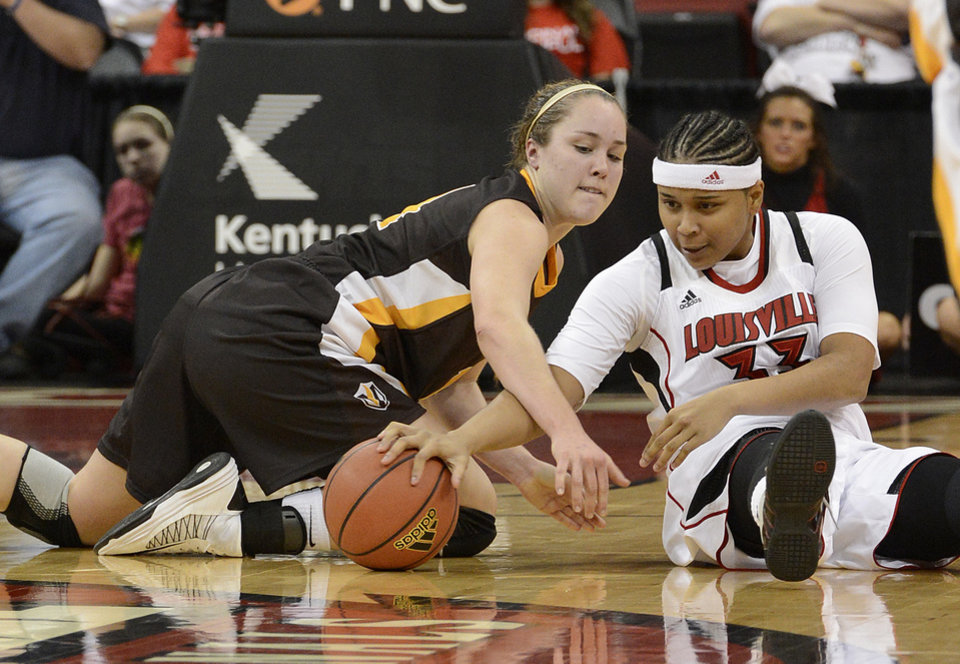 Photo - Louisville's Monique Reid, right battles Varparaiso's Tabitha Gerardot for a loose ball during the first half of an NCAA women's college basketball game Saturday Dec. 8, 2012, in Louisville, Ky. (AP Photo/Timothy D. Easley)