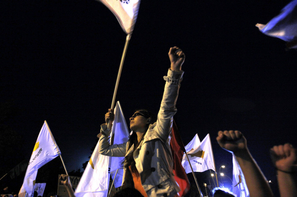Photo - A protestor waves a Cyprus' flag during a rally outside the Cypriot Presidential palace in capital Nicosia, on Wednesday, March 27, 2013.  Cypriot authorities are preparing limits on how much money depositors can take out of their accounts a day before banks are set to reopen. (AP Photo/Petros Karadjias)