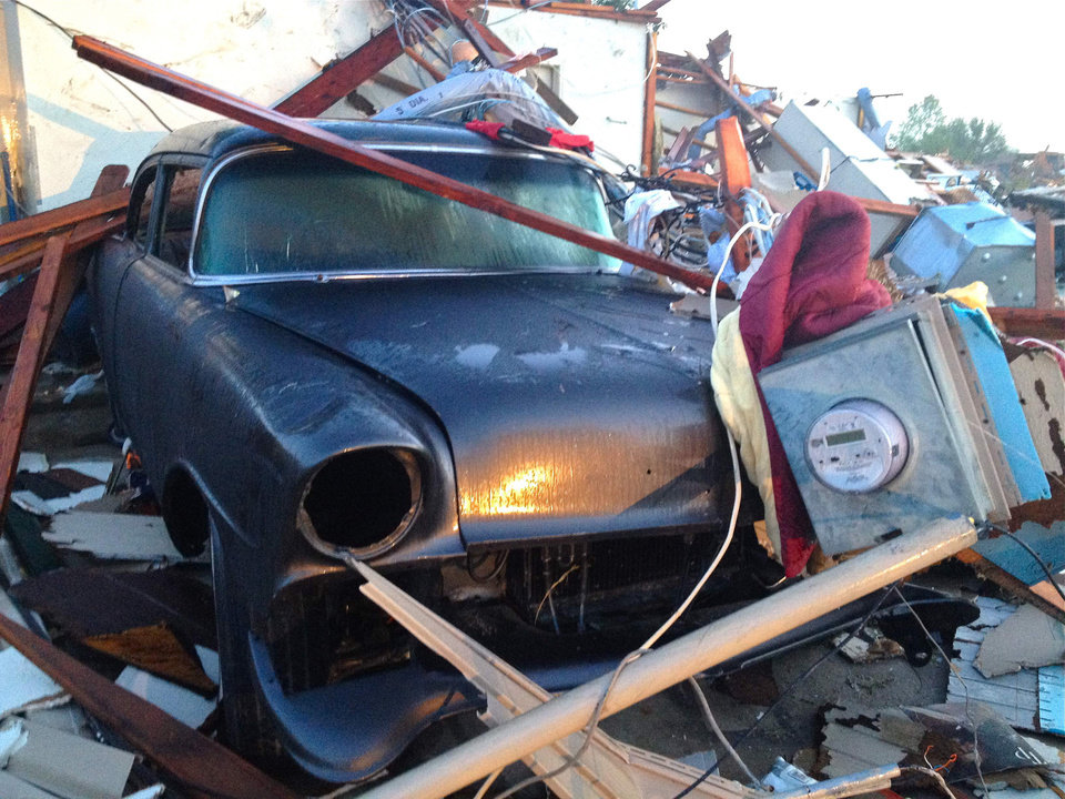 Photo -   A vehicle is covered in tornado debris in Dallas, Texas Wednesday, April 4, 2012. Storm surveyors are fanning across North Texas Wednesday trying to determine how many tornadoes touched down in the region Tuesday, as people sift through the debris that used to be their homes. The National Weather Service says possibly as many as a dozen twisters moved across the Dallas-Fort Worth area, bouncing in and out of neighborhoods, destroying homes at random. (AP Photo/Robert Ray)