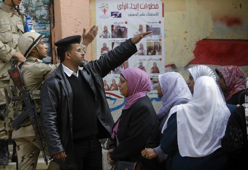 Photo - An Egyptian army soldier and a policeman direct voters in front of a polling station in Cairo, Egypt, Tuesday, Jan. 14, 2014. Egyptians have started voting on a draft for their country's new constitution that represents a key milestone in a military-backed roadmap put in place after President Mohammed Morsi was overthrown in a popularly backed coup last July. Arabic reads