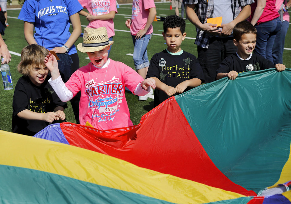 Photo - Carter Sudberry, 7, second from left wearing hat, of Ardmore, joins children from Northwoods Fine Arts Academy in Sand Springs as they toss varying size balls onto a multi-hued piece of fabric and then tug on it to raise and lower the balls. These children are participating in activities on 'Stars of the Future' area south of Boone Pickens Stadium on the Oklahoma State University campus on Thursday, May 15, 2014. Special Olympics athletes numbering in the thousands are competing in various events today and tomorrow  in Stillwater as the organization's 45th Annual Summer Games are held in Oklahoma this week.  Officials say more than 4,600 Special Olympics Oklahoma athletes have registered to compete this year, and thousands of volunteers are assisting during the three days of competitions.   This is the 31st year the summer games has been centered at Oklahoma State University.  Special Olympics is the world's largest sports organization for children and adults with intellectual disabilities, providing year-round training and competitions to more than 4.2 million athletes in 170 countries, according to their web site. Photo by Jim Beckel, The Oklahoman