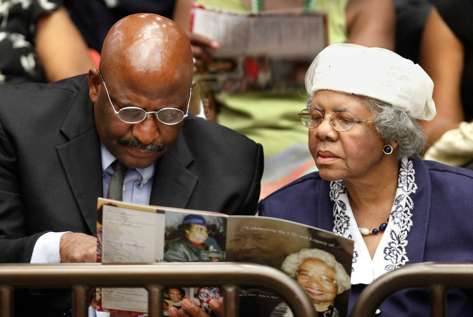 Photo - A man and a woman look at the program during the service.  About 2,500 people celebrated the life and legacy of Oklahoma City civil rights pioneer Clara Mae Shepard Luper  during a lively service in the Cox Convention Center that lasted more than three hours, Friday,  June 17, 2011.  Luper died  last week at the age of 88. Photo by Jim Beckel, The Oklahoman