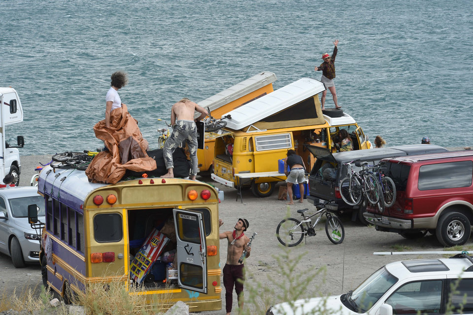 Photo - A woman dances on top of a van while other people set up camp on Blockhouse Beach at Pyramid Lake on Monday, Aug. 25, 2014, northeast of Reno, Nev. Thousands of Burning Man enthusiasts were on the outside looking in Monday after a rare batch of heavy rain forced organizers to temporarily close entry to the counterculture event in the desert 90 miles north of Reno. Many took advantage of the opportunity to camp at Pyramid Lake and made the best of the lake's beaches. (AP Photo/Reno Gazette-Journal, Tim Dunn)