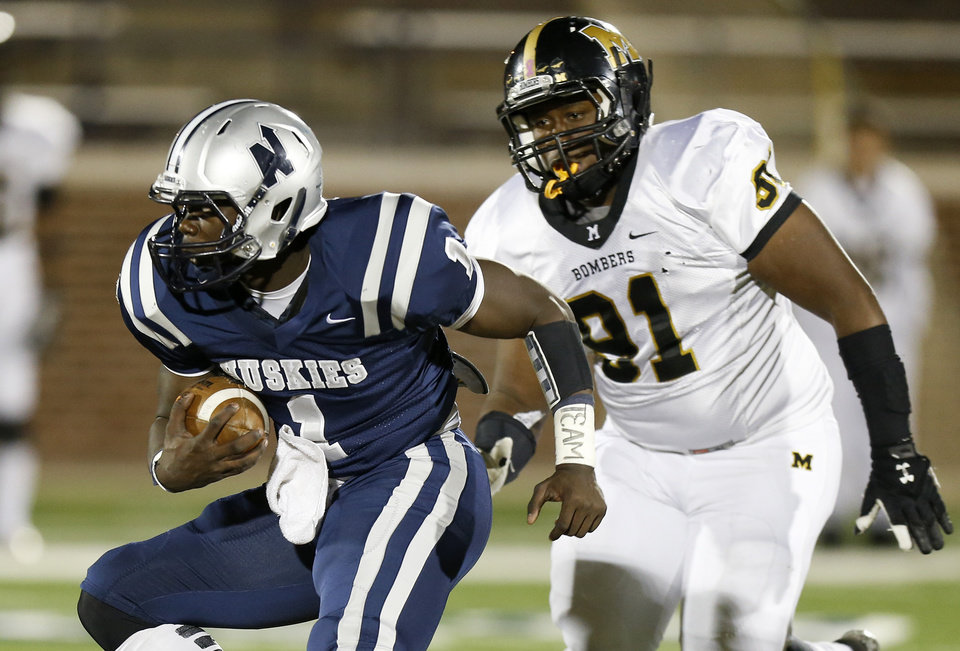 Edmond North's Michael Farmer runs past Midwest City's Brandon Jones on his way to a touchdown during a high school football game at Wantland Stadium in Edmond, Thursday, October 25, 2012. Photo by Bryan Terry, The Oklahoman
