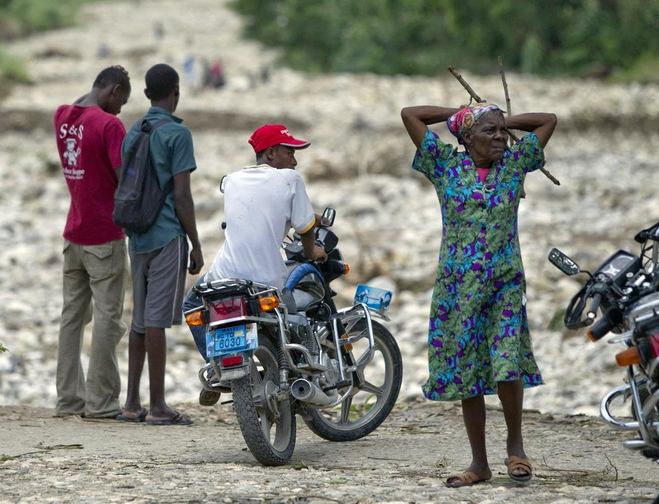 People react as they survey the damage in Jacmel, Haiti, a day after Tropical Storm Isaac brought rains and winds across the nation, Sunday, Aug. 26, 2012. At least seven people were killed by flooding in Haiti, including in tent cities filled with earthquake victims, and two others in the Dominican Republic. (AP Photo/The Miami Herald, Patrick Farrell) ORG XMIT: FLMIH107
