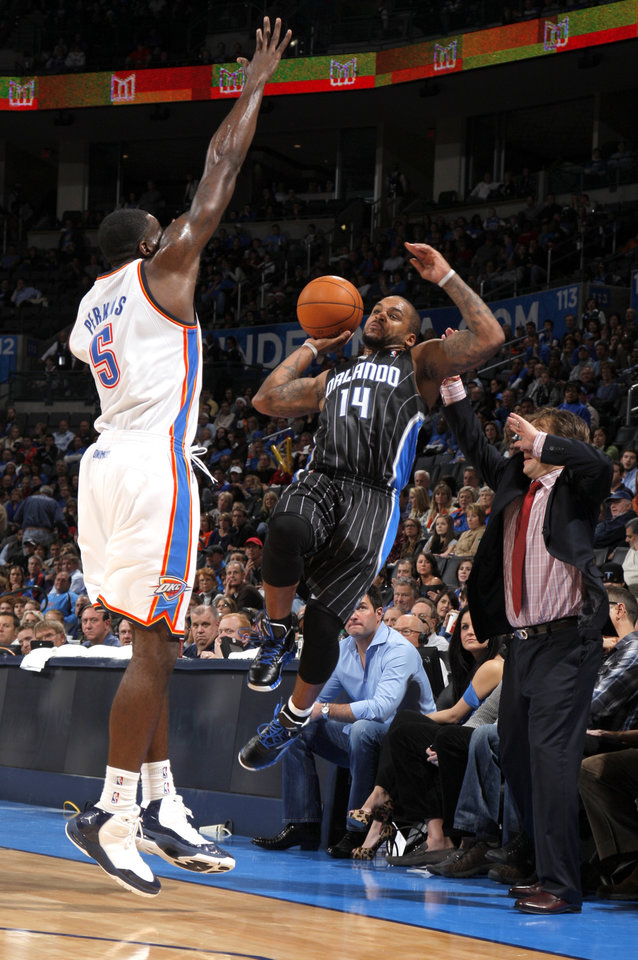 Photo - Orlando Magic's Jameer Nelson (14) tries to pass the ball as Oklahoma City Thunder's Kendrick Perkins (5) defends during the opening day NBA basketball game between the Oklahoma CIty Thunder and the Orlando Magic at Chesapeake Energy Arena in Oklahoma City, Sunday, Dec. 25, 2011. Photo by Sarah Phipps, The Oklahoman
