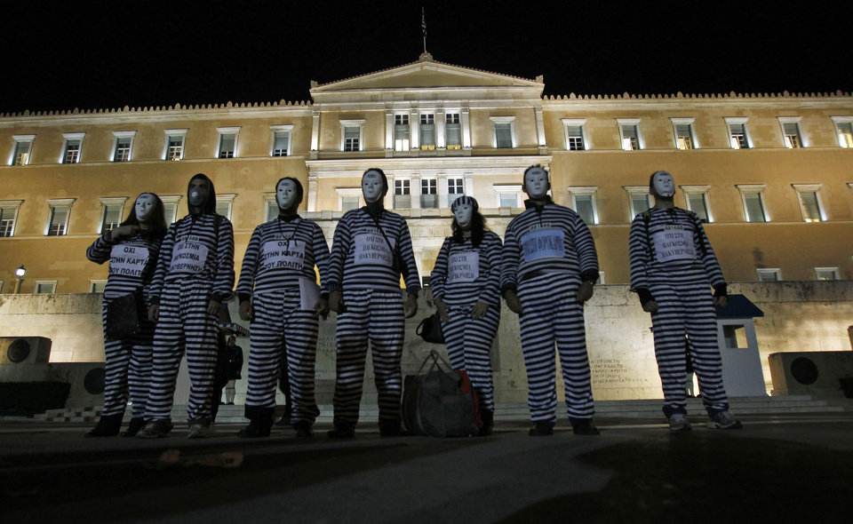 Protesters dressed as prisoners gather Tuesday outside the Greek parliament in Athens to protest against austerity measures. Lawmakers in Greece�s ruling Socialist party revolted Tuesday over their prime minister�s surprise decision to hold a referendum on a European debt deal. AP Photo