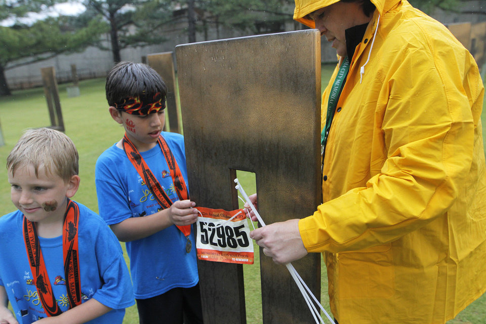 Helen Steifmiller, a museum curator, helps Jacob Bussey, 10, and Blake Bussey, 7, of Oklahoma City, attach their bibs to a chair at the Oklahoma City Memorial during the twelfth annual Oklahoma City Memorial Marathon in Oklahoma City, Sunday, April 29, 2012.  Photo by Garett Fisbeck, For The Oklahoman