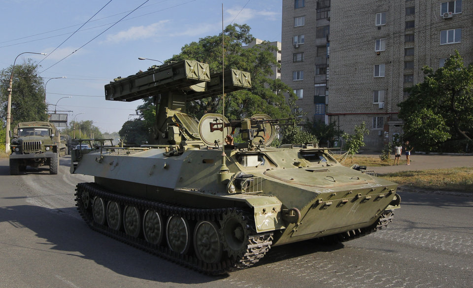 Photo - A Pro-Russian missile launcher drives in the town of Krasnodon, eastern Ukraine, Sunday, Aug. 17, 2014. A column of several dozen heavy vehicles, including tanks and at least one rocket launcher, rolled through rebel-held territory on Sunday.(AP Photo/Sergei Grits)