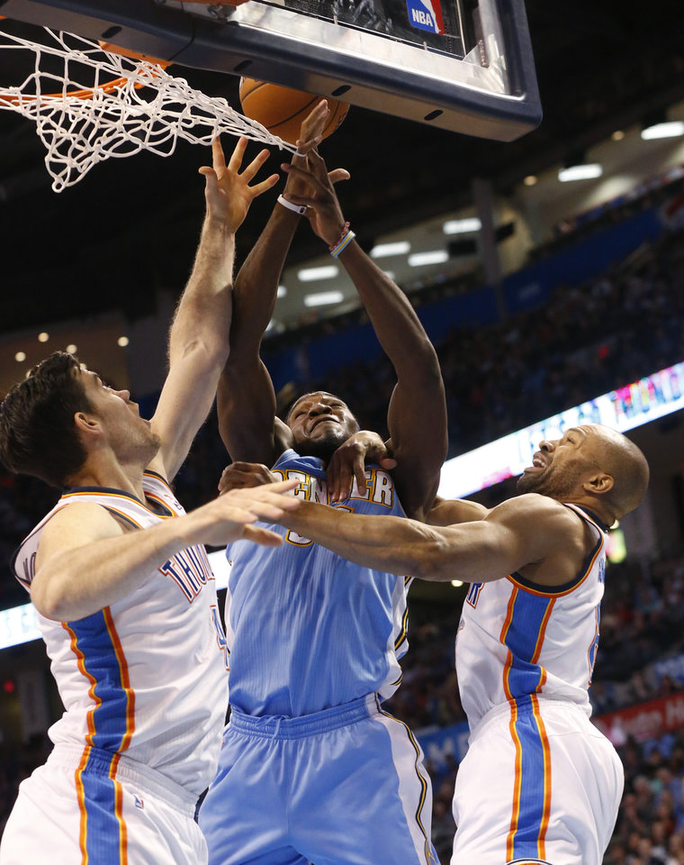 Photo - Denver Nuggets forward Kenneth Faried, center, loses the ball while defended by Oklahoma City Thunder forward Nick Collison (4) and guard Derek Fisher  in the first quarter of an NBA basketball game in Oklahoma City, Monday, March 24, 2014. (AP Photo/Sue Ogrocki)