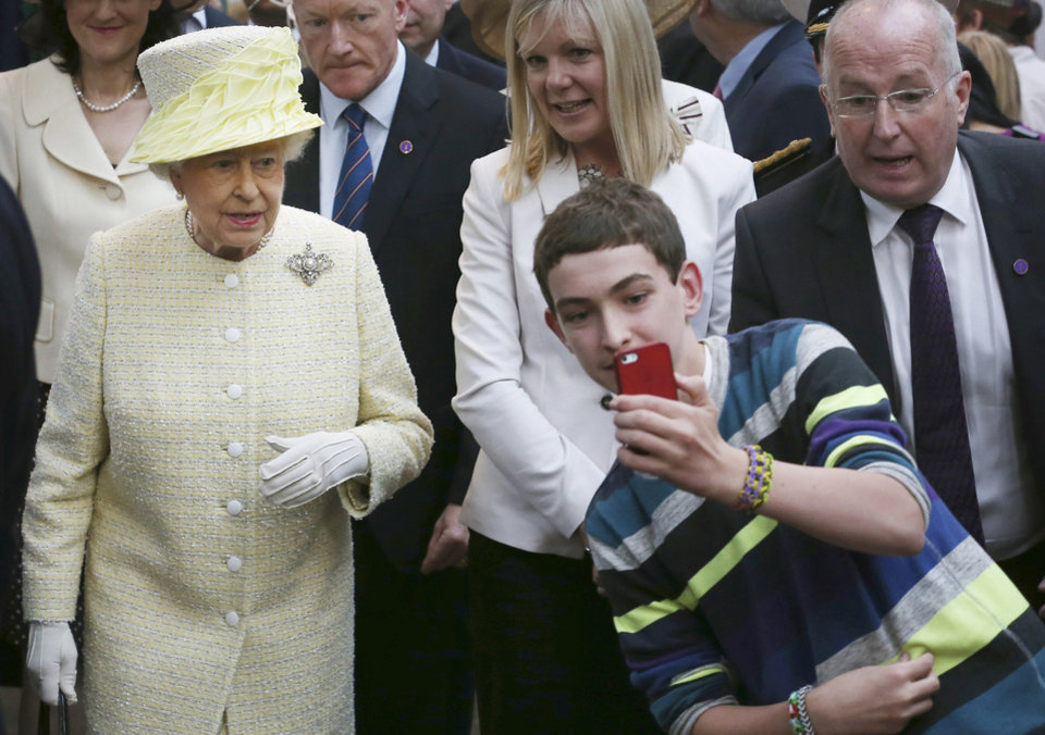 Photo - A local youth takes a selfie photograph in front of Queen Elizabeth II during a visit to St George's indoor market on  in Belfast Tuesday June 24, 2014. The Queen is on a 3 day visit to Northern Ireland .  (AP Photo/Peter Macdiarmid, Pool)