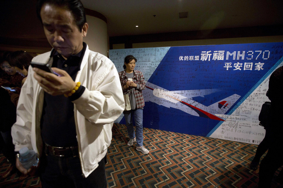 Photo - Relatives of Chinese passengers on board the missing Malaysia Airlines 370 wait in a room after walking out to protest the difficulties of communicating with Malaysian officials through video conferencing in Beijing, China, Wednesday, April 16, 2014. A robotic submarine looking for the lost Malaysian jet continued its second seabed search on Wednesday as up to 14 planes were to take to the skies for some of the final sweeps of the Indian Ocean for floating debris from the ill-fated airliner. (AP Photo/Ng Han Guan)