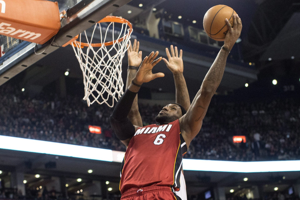 Photo - Miami Heat's LeBron James scores on Toronto Raptors' Amir Johnson during first half NBA basketball action in Toronto on Sunday, March 17, 2013. (AP Photo/THE CANADIAN PRESS,Chris Young)