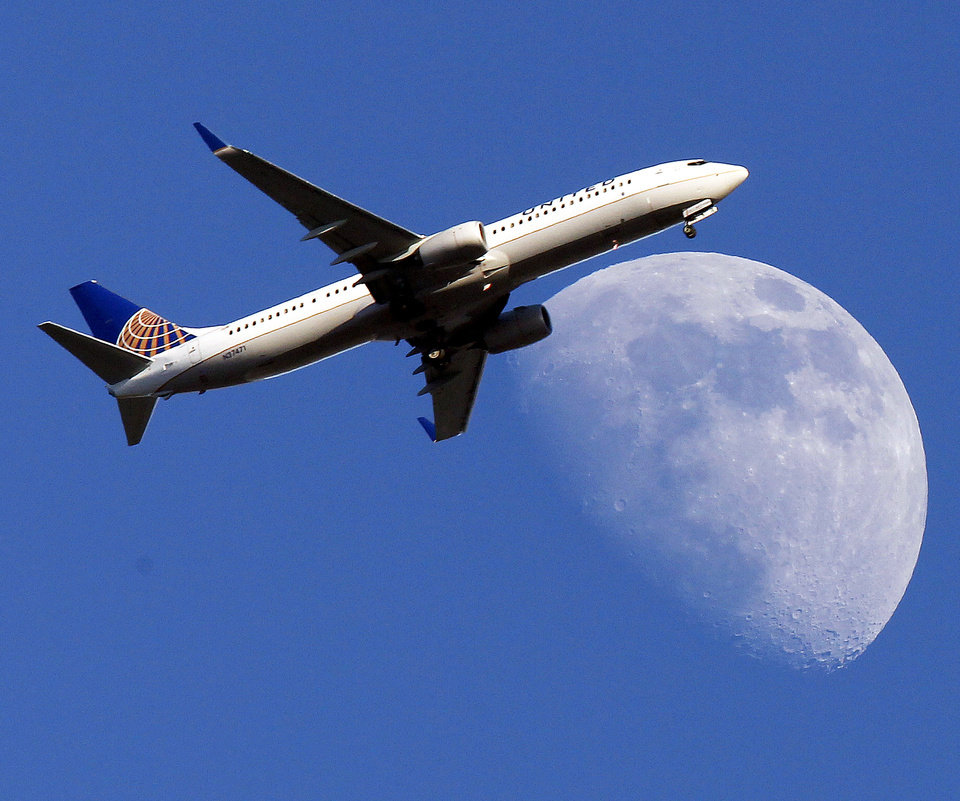 Photo - FILE - In this July 17, 2013 file photo, a United Airlines jet plane landing at Los Angeles International Airport, in Whittler City  Calif., passes in front of a Waxing Gibbous moon. United Airlines reports quarterly earnings on Thursday, April 24, 2014. ( AP Photo/Nick Ut, File)