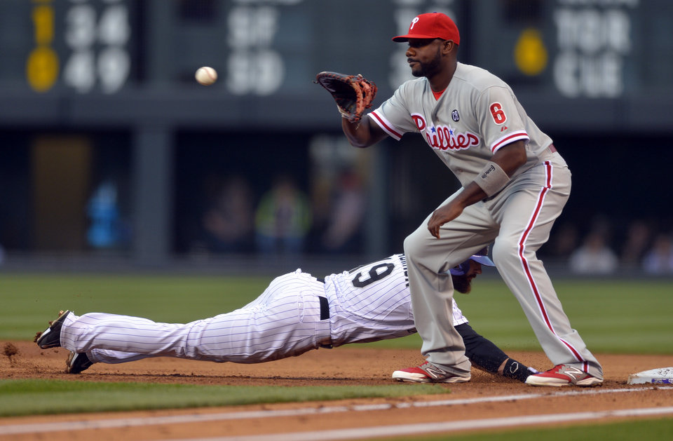 Photo - Colorado Rockies' Charlie Blackmon (19) beats the throw back to Philadelphia Phillies first baseman Ryan Howard (6) during the first inning of a baseball game on Friday, April 18, 2014, in Denver. (AP Photo/Jack Dempsey)