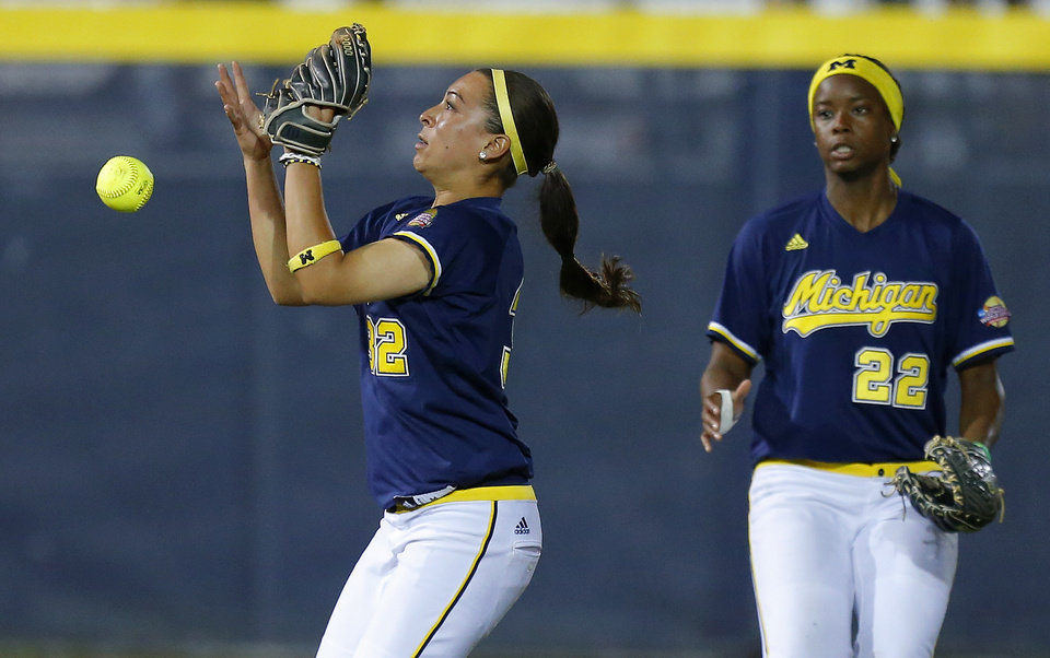 Michigan's Sierra Romero, left, drops the ball as Sierra Lawrence watches during their Women's College World Series softball game at ASA Hall of Fame Stadium in Oklahoma City, Sunday, June, 2, 2013. Photo by Bryan Terry, The Oklahoman