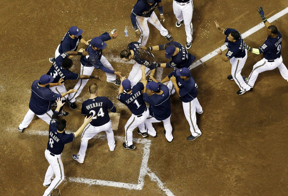 Photo - Milwaukee Brewers' Jonathan Lucroy celebrates with teammates after hitting a walk off home run during the ninth inning of a baseball game against the Cincinnati Reds, Tuesday, July 22, 2014, in Milwaukee. The Brewers won 4-3. (AP Photo/Morry Gash)