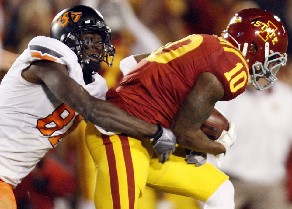 Photo - ISU's Jacques Washington (10) intercepts a pass by OSU's Brandon Weeden (not pictured) as Justin Blackmon (81) tackles Washington in the first quarter during a college football game between the Oklahoma State University Cowboys (OSU) and the Iowa State University Cyclones (ISU) at Jack Trice Stadium in Ames, Iowa, Friday, Nov. 18, 2011. Photo by Nate Billings, The Oklahoman