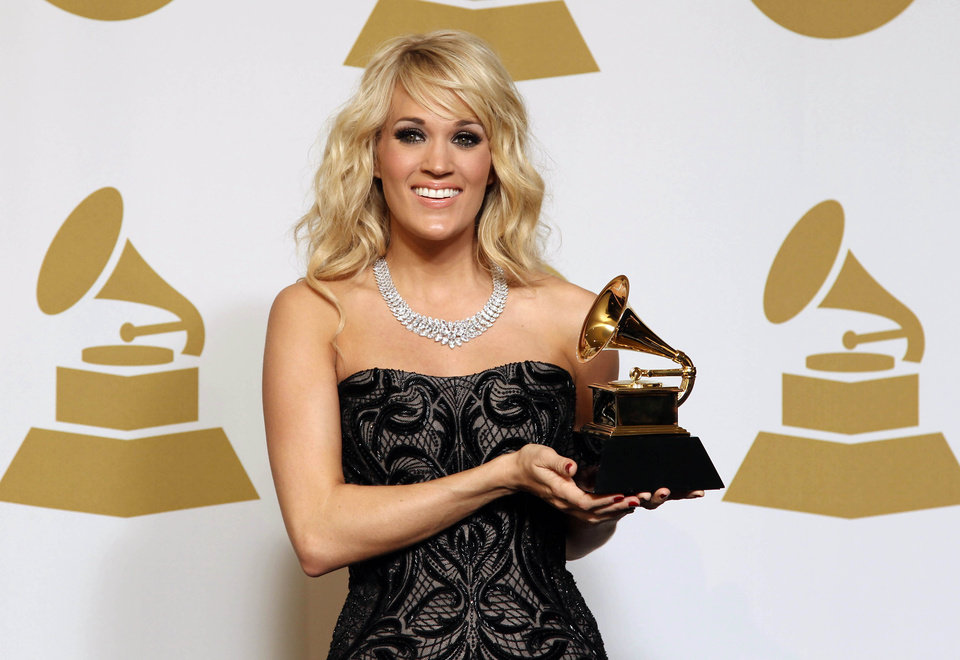 "Carrie Underwood poses backstage with the award for best country solo performance for ""Blown Away"" at the 55th annual Grammy Awards on Sunday, Feb. 10, 2013, in Los Angeles. (Photo by Matt Sayles/Invision/AP) ORG XMIT: CASH196"