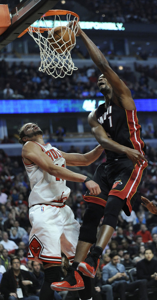 Photo - Miami Heat's Chris Bosh (1) dunks over Chicago Bulls Joakim Noah during the first quarter of an NBA basketball game in Chicago, Sunday, March 9, 2014. (AP Photo/ Paul Beaty)