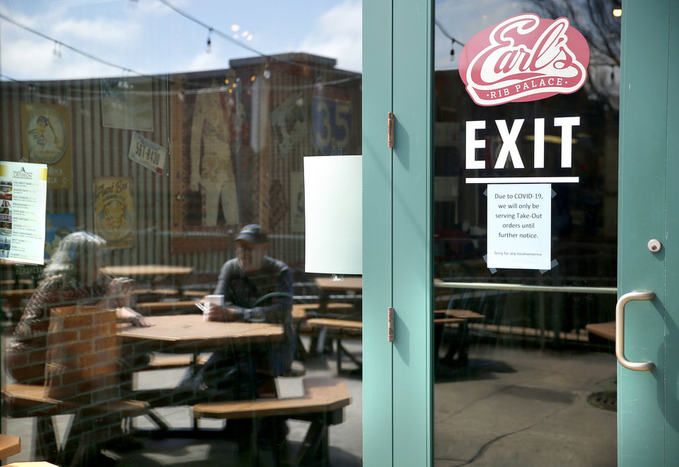 Photo - The reflection of Mike Younger and Debby Warren as they eat outside at Earl's Rib Palace can be seen in the doors in Bricktown in Oklahoma City, Wednesday, March 18, 2020. [Sarah Phipps/The Oklahoman]