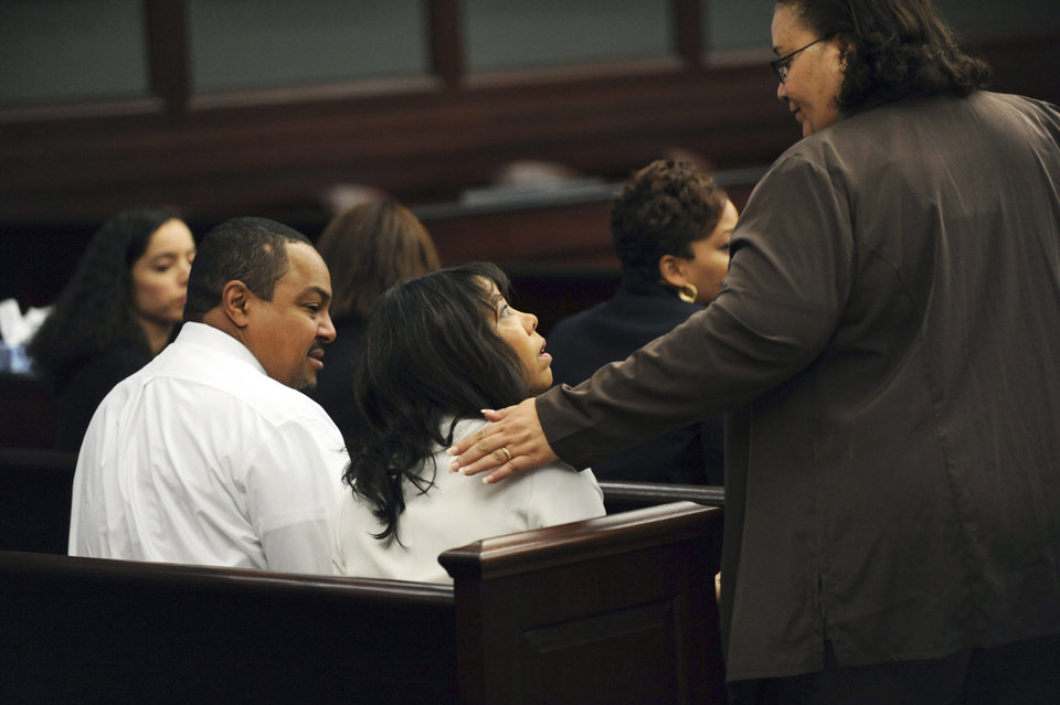 Photo - Lucia McBath, center, mother of Jordan Davis, is greeted by an unidentified woman who sat with the family in the courtroom, Saturday, Feb. 15, 2014 in Jacksonville, Fla. Her husband, Curtis McBath sits to her left. A jury begins their fourth day of deliberations Saturday in the trial of Michael Dunn, who is charged with fatally shooting 17-year-old Jordan Davis after an argument over loud music outside a Jacksonville convenient store in 2012. As of Friday, they had deliberated for 22 hours over three days. (AP Photo/The Florida Times-Union, Bob Mack, Pool)